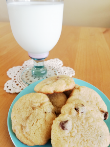 glass of milk on a crocheted doily with a blue plate full of chocolate cookies - Adventures in NanaLand - Becoming a grandparent