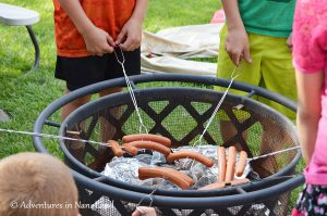 Kids roasting hotdogs on sticks over a backyard firepit at Grandma Camp