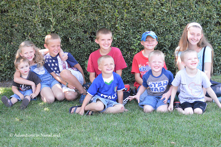 Children sitting on the grass, cousins, creating a schedule for grandma camp