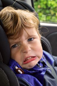 Grandchild with angry face sitting in carseat