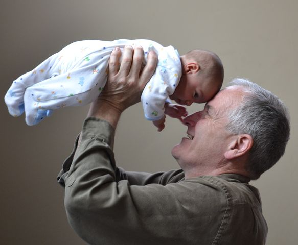 Grandfather holding new grandchild, grandparents