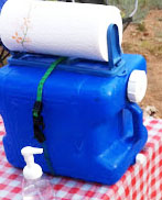 DIY hand washing station for camp, 5 gallon blue bucket with spigot and roll of paper towels strapped to top