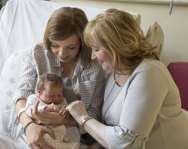Three generations of women - newborn baby, mom and grandma in hospital room