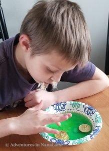 Boy discovering gold coins that were hidden inside baking soda rocks covered in vinegar - Magic Rainbow Rocks - Adventures in NanaLand
